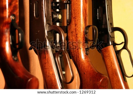 Close up of several rifles inside a weapons cabinet - stock photo