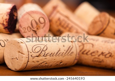 "Close-Up of several Wine Corks on wood. You can read "" Mis en Bouteille"" (which means ""filled in the bottle or bottled"") or the Origin of the Wine and or the Vintage on them. - stock photo"