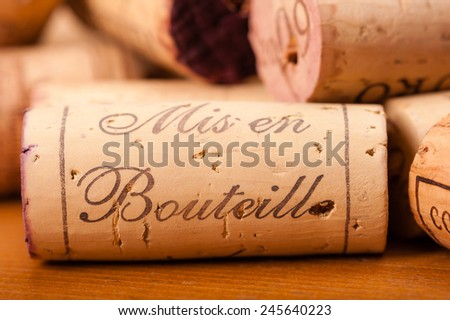 "Close-Up of several Wine Corks on wood. You can read "" Mis en Bouteille"" (which means ""filled in the bottle or bottled"") and or the Vintage on them. - stock photo"