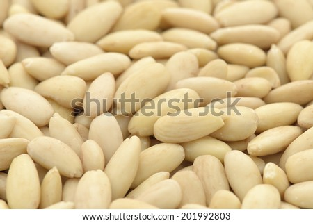 Close-up of shelled and blanched almonds kernel to use as background  - stock photo