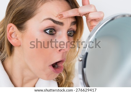 Close-up Of Shocked Woman Looking At Pimple In Mirror - stock photo