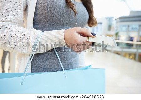 Close Up Of Shopper Holding Credit Card And Bag In Mall - stock photo
