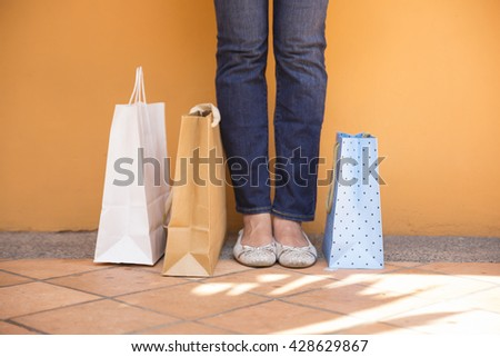 Close up of shopping bags and a womans feet while standing on an urban street.  - stock photo