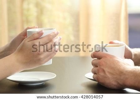 Close up of side view of a couple or friends talking with hands holding coffee cups on a table with a window and curtain in the background - stock photo