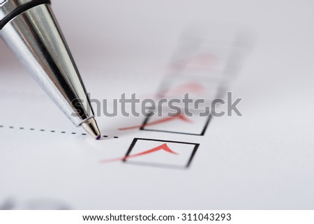 Close-up Of Silver Pen Over Filled Checkboxes In Form - stock photo