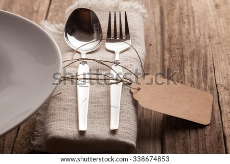 Close Up of Silver Spoon and Fork Tied with Twine and Blank Tag on Natural Napkin with Fringed Edges Beside Neutral Plate and Set on Rustic Wooden Table with Copy Space - stock photo
