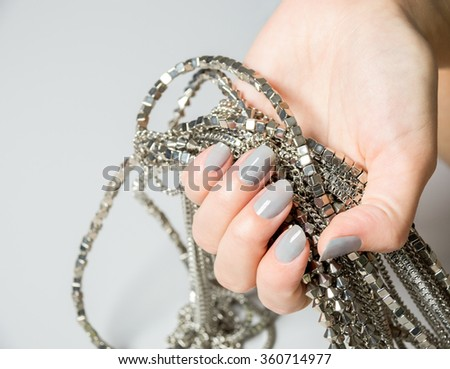 Close up of single Caucasian hand holding bundle of necklaces - stock photo