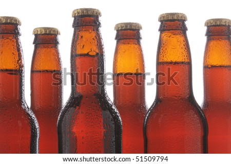 Close up of six brown beer bottles with condensation. Horizontal format over a white background - stock photo