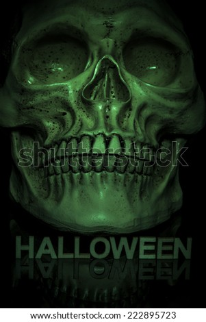 Close up of skull with letters below spelling out the word halloween and lit by a green light to give a spooky green glowing skull on a black background - stock photo