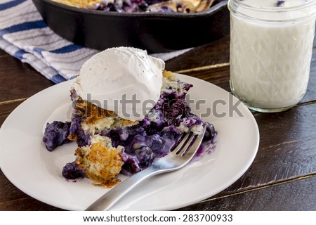 Close up of slice of fresh baked blueberry cobbler sitting on white plate with fork topped with vanilla bean ice cream and glass of milk - stock photo