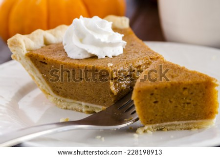 Close up of slice of homemade pumpkin pie sitting on white plate with whipped cream and fork cutting into pie - stock photo