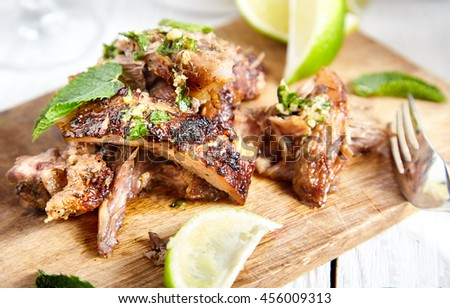 Close up of sliced cuban style slow roasted pork shoulder in mojo marinade and sauce on wood board with limes and mint near it. White wood background with brown rice bowl and pan on back - stock photo