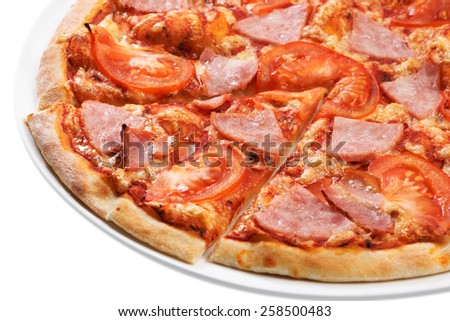 Close up of sliced pizza with tomatoes, meat and ham - stock photo