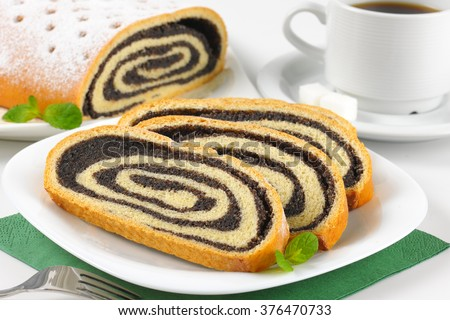 close up of sliced poppy seed roll on white plate - stock photo