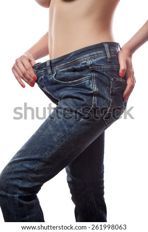 Close-up of slim waist of young woman in big jeans showing successful weight loss, isolated on white background, diet concept - stock photo