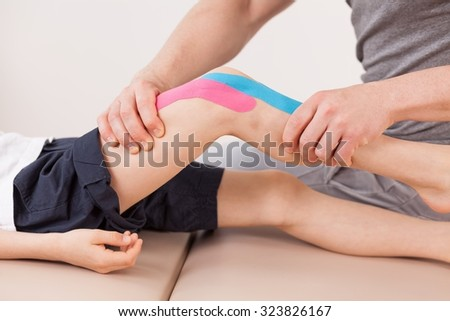 Close up of small boy with kinesio tape doing exercises - stock photo