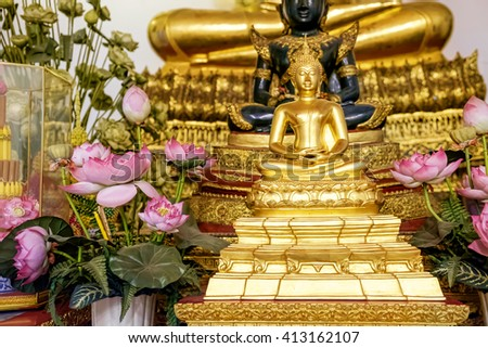 Close Up Of Small Golden Buddha Statue In Lotus Position With Flowers At Wat Pho, Bangkok, Thailand. Buddhism. Praying, Meditation. Religious Buddhist Symbol - stock photo