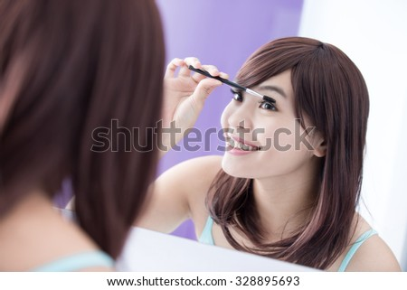 Close up of Smile woman applying mascara on her long eyelashes and look mirror. asian beauty - stock photo