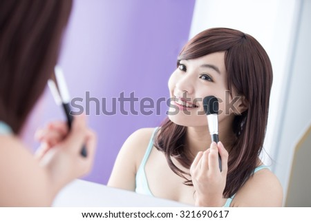 Close up of Smile woman with makeup brushes near face and look mirror. asian beauty - stock photo