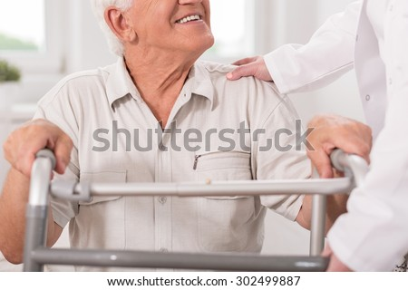 Close up of smiling senior man with walking zimmer - stock photo