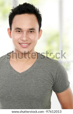 close up of smiling young asian man - stock photo
