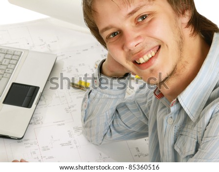 Close-up of smiling young businessman at his workplace - stock photo