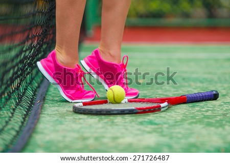 Close up of sneakers near the tennis racquet and ball - stock photo