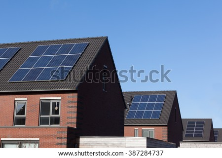 Close up of solar panels on family houses producing alternative energy - stock photo