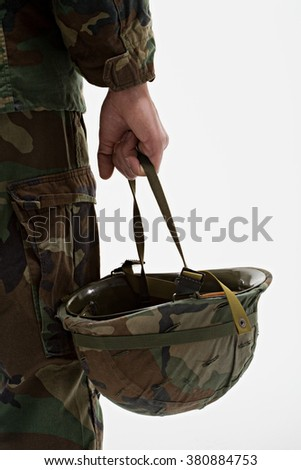 Close up of soldier holding helmet - stock photo