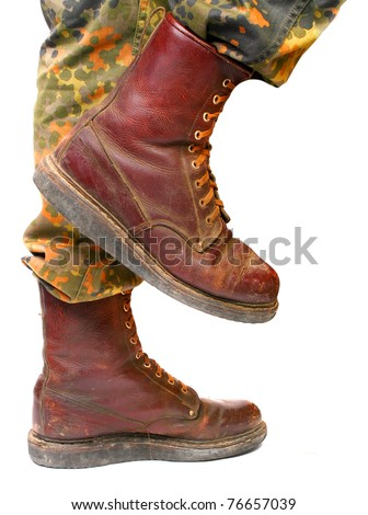 Close up of soldier legs in old army paratroopers combat boots on a white background. - stock photo