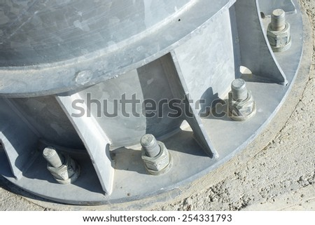 Close up of some larger screws into the base of a metal pillar. - stock photo