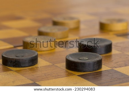 Close up of some old checkers on checker board - stock photo