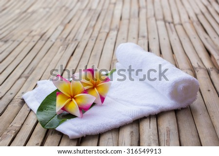 close up of spa treatment mini set  on old vintage bamboo backgrounds : close up of plumeria red flowers with leaf and rolling white towel .natural outdoors spa treatment concept.healthy life concept. - stock photo