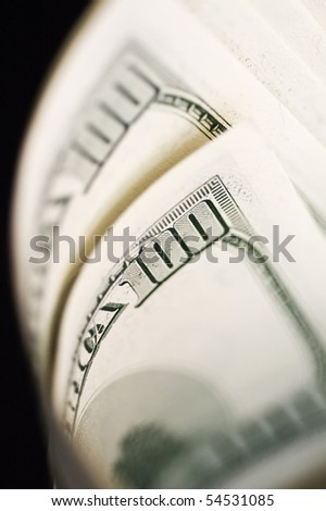 Close Up of Stack of dollars isolated on black background. - stock photo