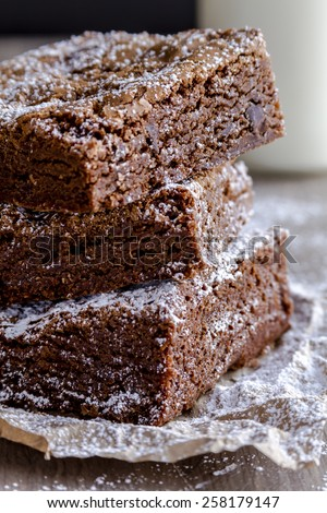 Close up of stack of homemade double chocolate chunk brownies dusted with powdered sugar and glass of milk - stock photo