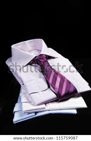Close up of stacked shirts with tie. - stock photo