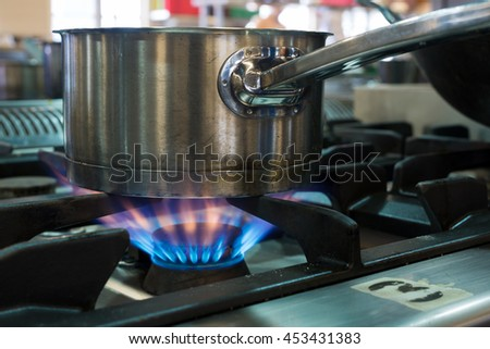 close up of stainless sauce pan standing on the stove - stock photo