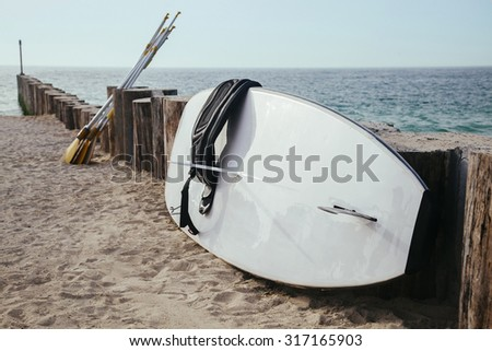 Close Up Of Stand Up Paddle Board And Oar On The Beach - stock photo