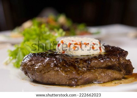Close Up of Steak Topped with Herbed Butter and Garnish on Plate - stock photo