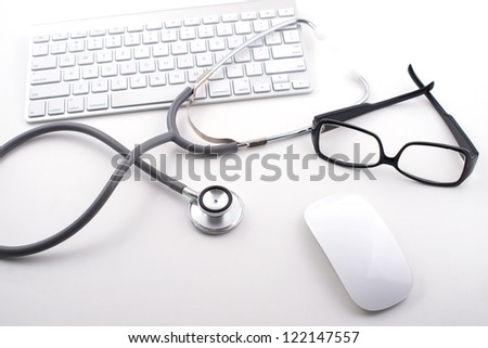 Close-up of stethoscope and glasses on keyboard - stock photo