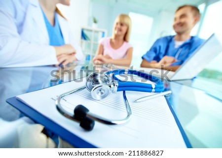 Close-up of stethoscope and paper on background of doctors and patient - stock photo