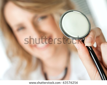 Close-up of stethoscope, being held by female Blondie doctor, focus on instrument - stock photo