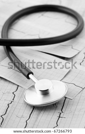 Close-up of stethoscope on cardiograms. Monochrome B&W image. - stock photo