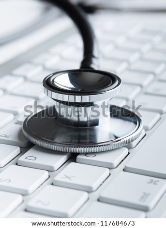 Close up of stethoscope on laptop keyboard. Medicine concept - stock photo