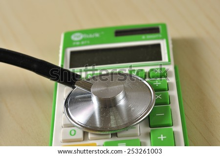 Close Up of Stethoscope with Calculator on Desk, Medical Cost Concept and Selective Focus  - stock photo
