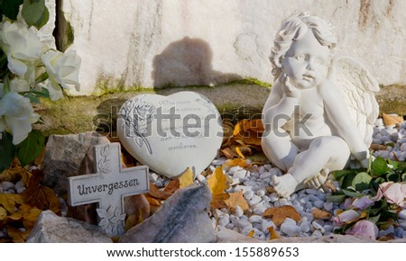 Close up of stone heart and cross with angel - stock photo