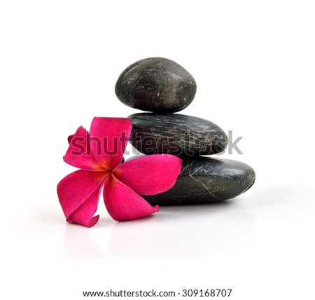 Close up of stones pyramid with a plumeria flower, isolated on white background. - stock photo