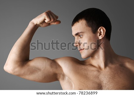 Close-up of strong muscular man over grey background - stock photo