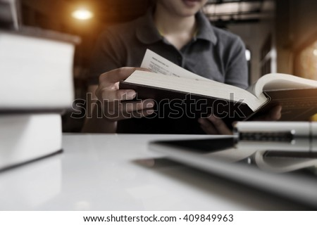 Close up of student hand reading a book with laptop at library vintage tone. - stock photo