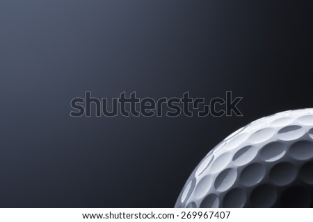 Close up of stylish golf ball isolated on dark blue background, copy space for text. - stock photo